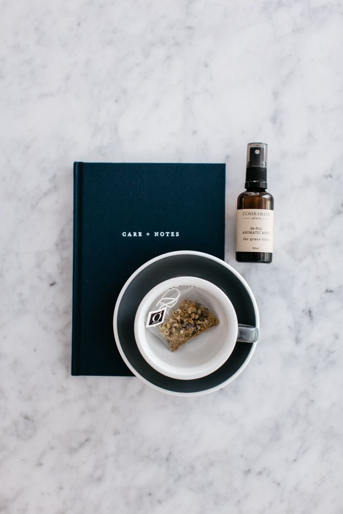An image of The Grace Files Care + Notes journal, tea cup, organic tea and aromatic mist. These items are all part of our get well care package, the Calm Kindness Kit.