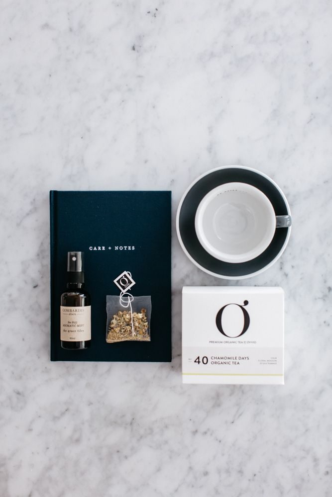 An image of The Grace Files Calm Kindness Kit showing the Care + Notes journal, tea cup, calming mist and organic tea. A perfect get well care package.