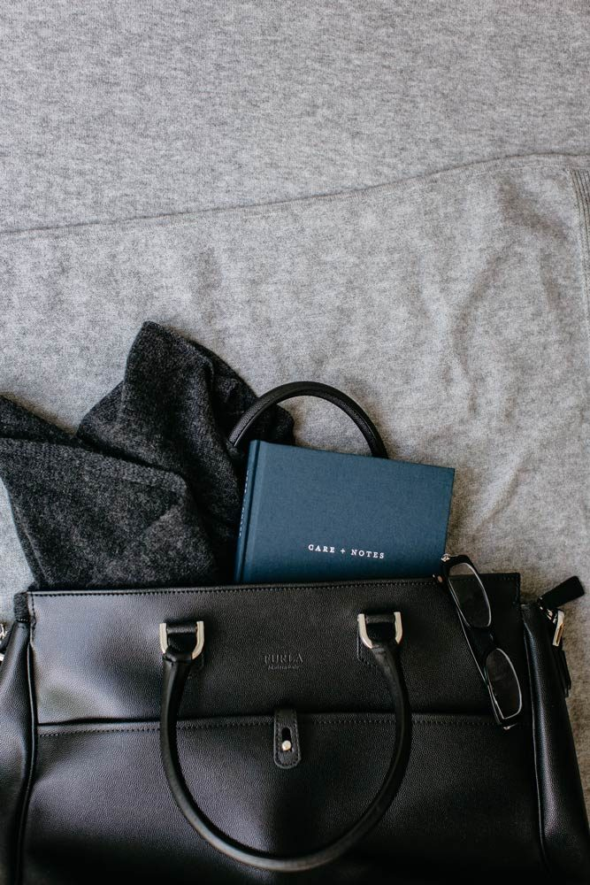Image showing The Grace Files Care + Notes journal, and a cashmere shrug in a black Prada bag. The journal and shrug make perfect gifts for someone going in for a long hospital stay.