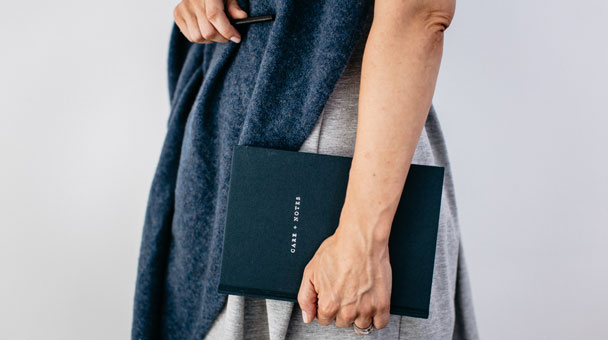 Image of a person wearing The Grace Files cashmere hug and holding our get well soon gift, The Grace Files Care + Notes journal