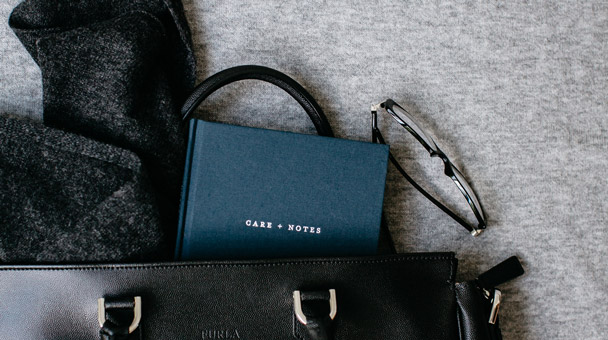 Image of The Grace Files Care + Notes journal sticking out of a black bag.