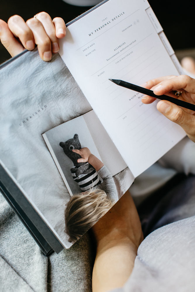 A photo of a mum writing in our Life + Notes journal, part of The Grace Files Bear + Life Kindness Kit. A unique baby shower gift.