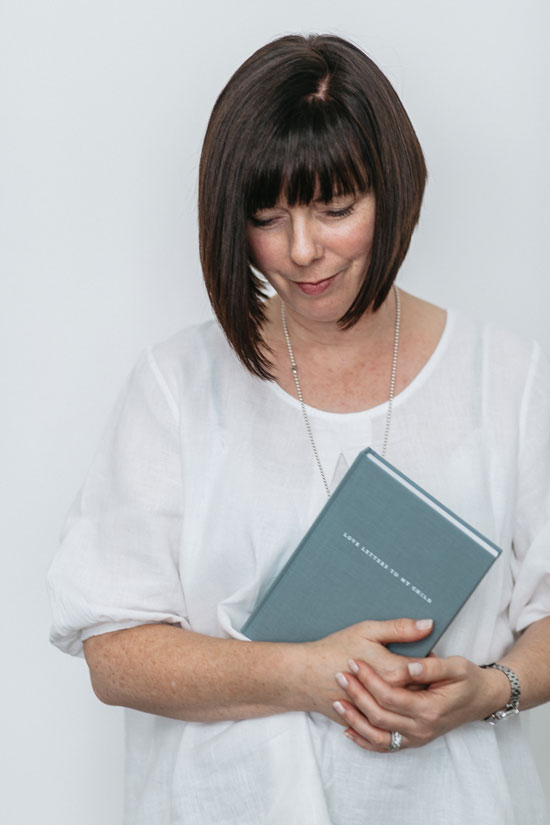 A photo of The Grace Files founder Janelle Ruthven holding a Love Letters To my Child journal