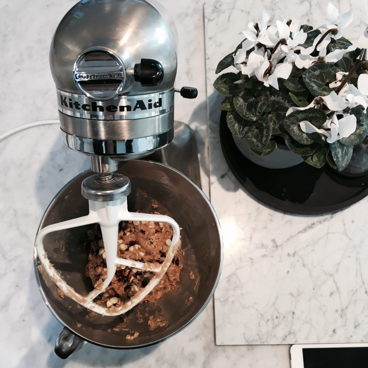 Image of a Kitchen Aid mixer mixing up a cookie dough mixture on a marble work bench.