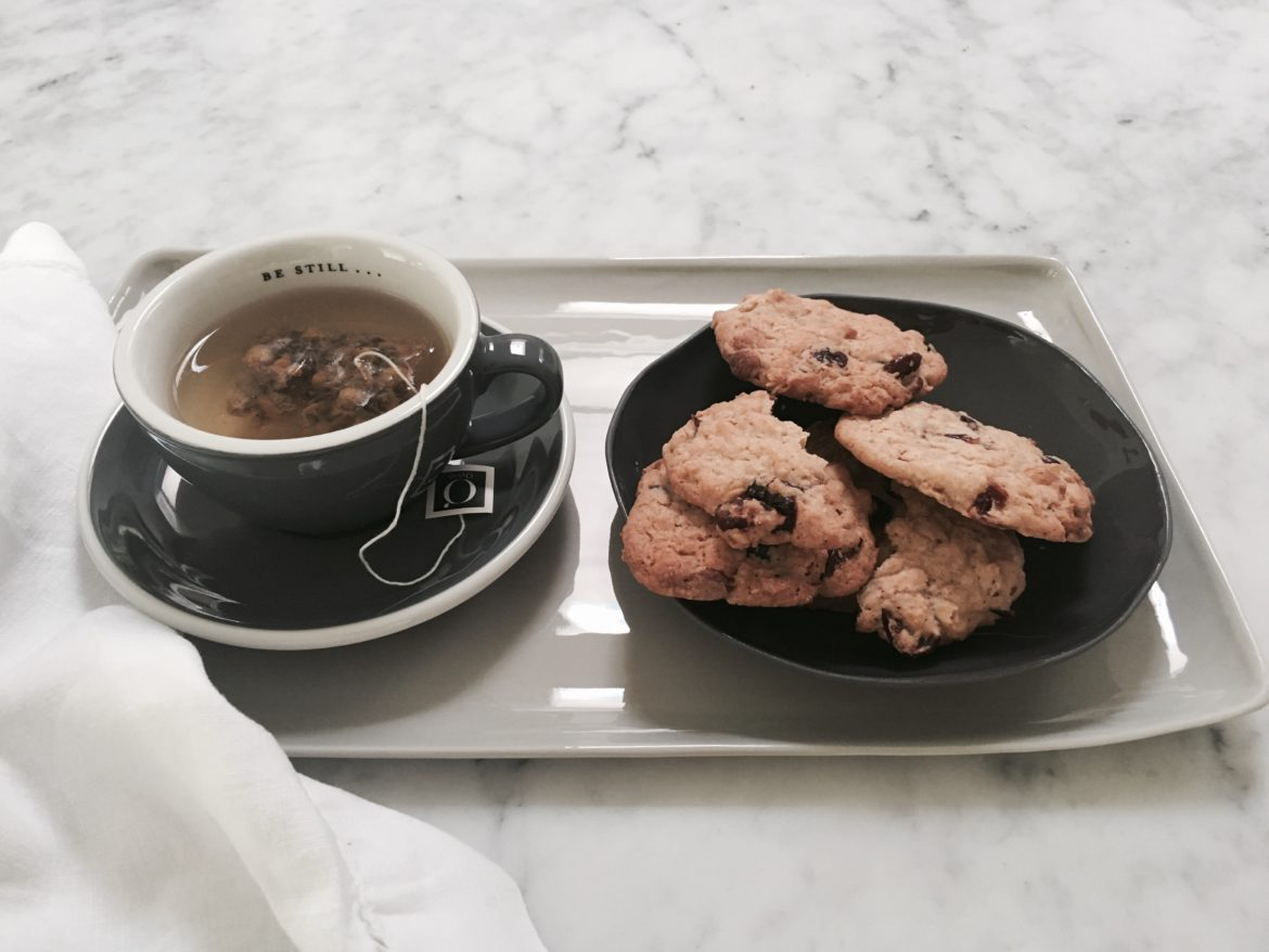 Image of a cup of tea and cookies on a tray.